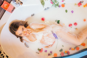 beautiful pregnant woman in a bathroom with milk and flowers.