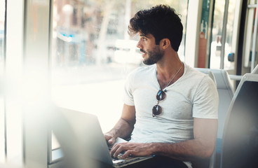 Bearded hipster guy is working on a portable computer connected to public wi-fi while sitting in a city bus. Young attractive male is looking at the window while typing messages by a laptop. Wall mural