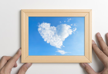 Hands holding picture frame with cloud heart