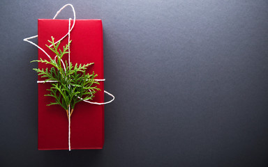 Christmas handmade gift boxes decorated with red paper, green branch on dark grey background top view. Merry christmas greeting card. Winter xmas holiday theme. Happy New Year. Space for text.