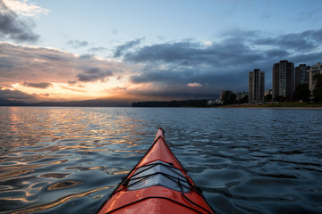 Kayaking near Downtown Vancouver during a cloudy and colorful sunset. Taken in British Columbia, Canada.