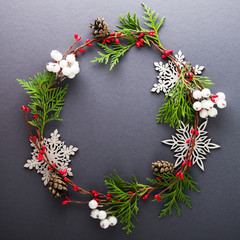 Frame with christmas wreath, berries, snowflakes and balls on dark background top view. Merry christmas greeting card, banner. Winter xmas holiday theme. Happy New Year. Space for text. Flat lay.