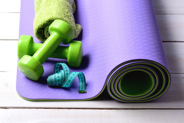 Shaping and fitness equipment. Barbells near cyan measuring tape roll