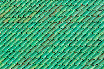 Vibrant green roof tiles. Patterned and textured background image of colored tiles