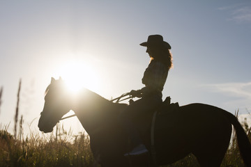 Silhouette of a woman in cowboy hat riding a horse - sunset or sunrise, horizontal