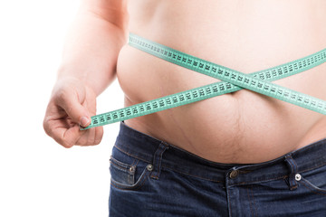 Overweight man measuring fat on his belly with green centimeter tape. Fat folds with scar closeup isolated on white background. Obesity concept