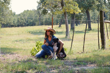 Woman in western cowboy hat happy and holding her cute pet dog on the farm.