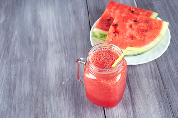 Chopped pieces of watermelon on a white plate and a glass mug with a watermelon smoothie