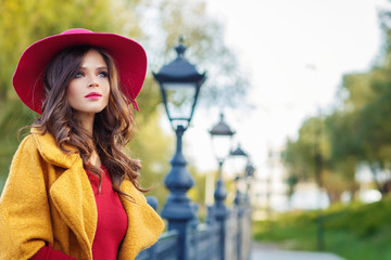 Young beautiful women in a yellow coat and a red hat, outdoor