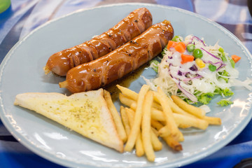 Grilled sausage with sauce and Fresh salad and French fries