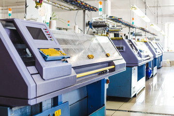Textile industry with knitting machines in factory. Knitting and weaving machines in textile industry
