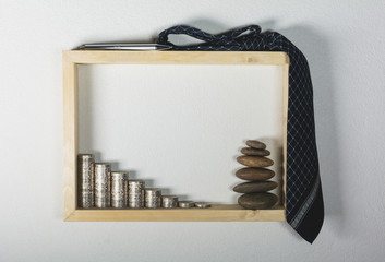 stack coin with pen and necktie in wooden frame on white wall background. Financial and saving concept.