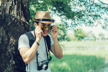Young man tourists shooting vintage camera and backpack, shooting style, travel style in the forest.