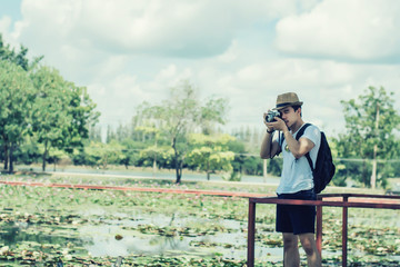 Young man tourists shooting vintage camera and backpack, shooting style, travel style in the park.