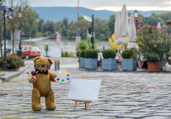 Teddy bear painting a picture on a european street