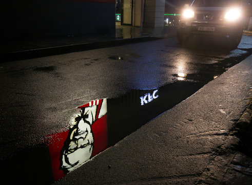 A KFC logo is seen in a puddle as a car leaves the drive through in Hillcrest