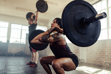 Woman doing front squats at gym