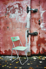 A plastic chair by a painted metal gate