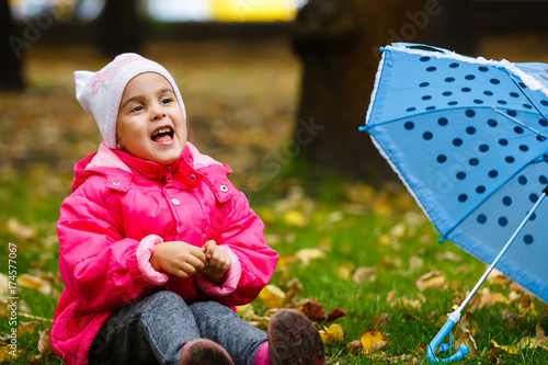 5d2928202 smiling little girl with umbrella in raincoat and boots outdoor ...