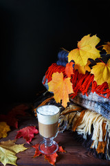 stack of warm woolen blankets of colorful in autumn style and a glass cup with cappuccino coffee with maple leaves on a wooden background