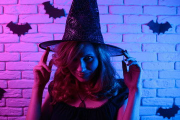 Happy gothic young woman in witch halloween costume partying in a nightclub, image with free space for design. Halloween, celebration, party concept