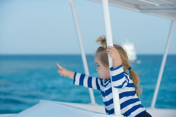 Boy child with serious face sailing in white yacht