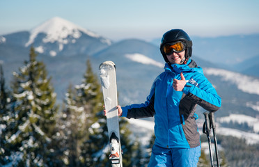 Close-up portrait of happy female skier showing thumbs up on top of a mountain with her skis, smiling joyfully incredible winter scenery on the background copyspace