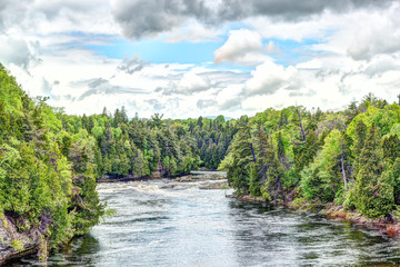 Montmorency river in Boischatel town, city of Quebec landscape during cloudy, overcast day with pine tree forest, current, cloudy sky, clouds