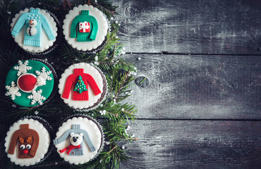 Homemade Christmas cupcakes on wooden background with blank space