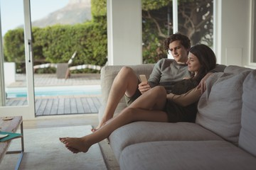 Smiling couple using mobile phone in living room