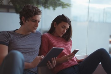 Smiling couple using digital tablet and mobile phone in living