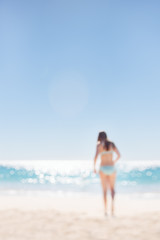 Teenage girl in a turquoise bikini walking to the sparkling water of the Indian Ocean