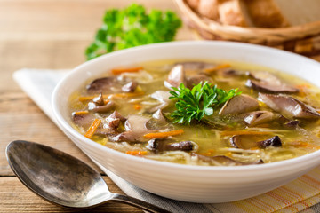 Chicken soup with mushrooms and noodles on rustic wooden table