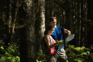 Couple with map standing in the forest