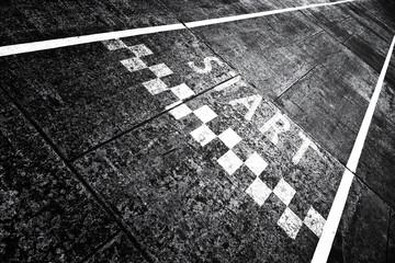 Grunge textured start pattern line sign on the asphalt road.