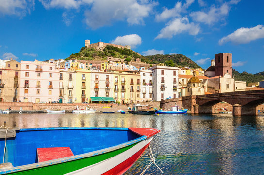 Colourful boat on background of beautiful buildings of Bosa, Sardinia, Italy