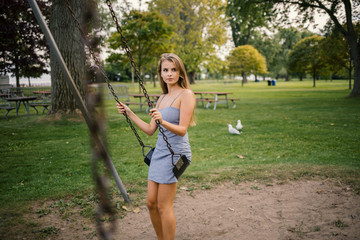 Young woman on swing in park