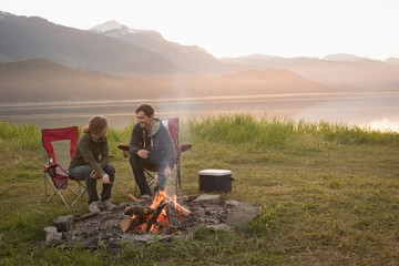 Couple enjoying time together near campfire at campsite