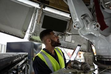 Male aircraft maintenance engineer examining engine of an