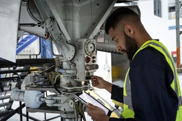 Male aircraft maintenance engineer examining engine of an
