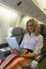 Woman using digital tablet while sitting in an aircraft seat