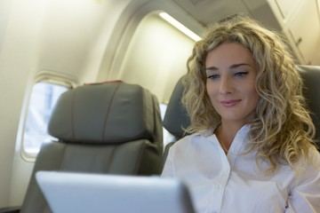 Woman using digital tablet while travelling in an aircraft seat