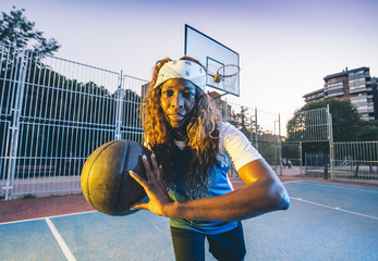 African woman poses with basket ball...