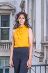 Portrait of Modern East Indian American Lady. Wearing sleeveless orange shirt, striped pants, a beautiful business woman with long curly hair standing by vintage style office building, looking at you.