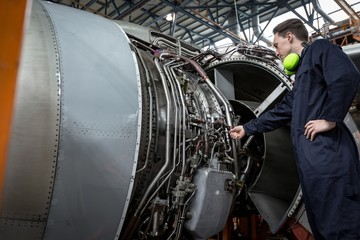 Male aircraft maintenance engineer examining turbine engine of