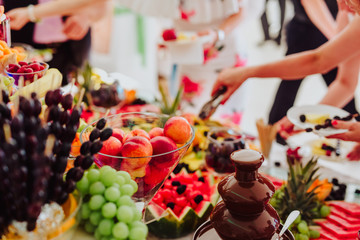 people group in the line catering buffet food indoor in luxury restaurant with colorful fruits and chocolate