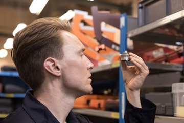 Male aircraft maintenance engineer examining various work tool