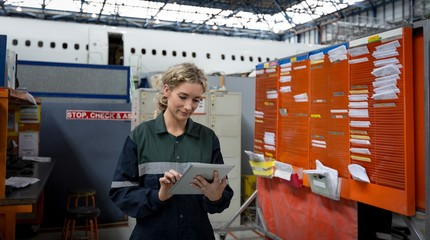 Female aircraft maintenance engineer using digital tablet