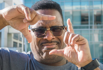 close up of black man with fingers making a square around eyes