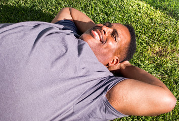 close up of smiling middle aged black man lying on grass